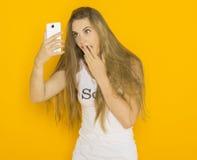 不快乐的年轻可爱的妇女非常使某事惊奇在她的智能手机 免版税图库摄影