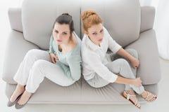 不快乐的年轻女性朋友不谈话在长沙发的论据以后 图库摄影