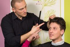 不快乐的年轻男性画象在理发沙龙的 免版税库存图片