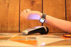 不接触的付款苹果手表pdq背景拷贝空间用拿着信用卡的手支付 库存照片