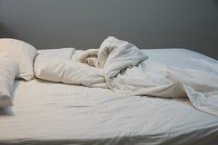 不整洁毯子,在床上的枕头 免版税库存照片