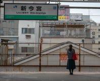 不明身份的唯一Japansese夫人在大阪,日本在ShinImamiya驻地等待客车 库存图片