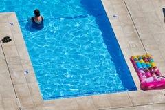 不明身份的妇女在一游泳场变冷静在一烧焦的热的天 免版税库存图片