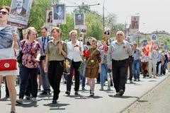 不朽的军团的参加者与走沿街道的他们的亲戚画象的在胜利天在伏尔加格勒 免版税图库摄影