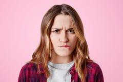 不满意的女性画象的关闭弯曲嘴唇并且皱眉面孔,懊恼作为与某人的争吵,表现出消极情感 库存图片