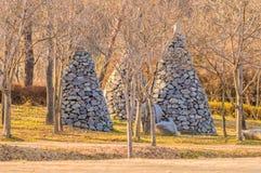 不生叶的树围拢的三座石金字塔 免版税库存图片