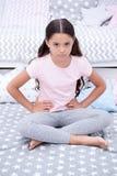 不要在睡眠前干扰孩子 女孩孩子坐床在她的卧室 不快乐的孩子某人进入了她的卧室 库存照片