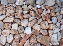 不规则的宽松石墙由与在表面交织的老枝杈的大织地不很细褐色和白色石灰石岩石做成 库存图片