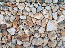 不规则的宽松石墙由与在表面交织的老枝杈的大织地不很细褐色和白色石灰石岩石做成 免版税库存照片