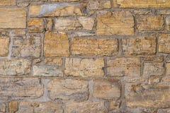 不规则的老沙子石墙 免版税库存照片