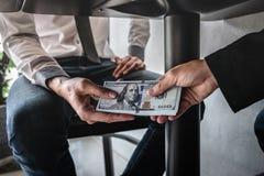 不诚实欺诈在企业非法金钱,商人收到贿款金钱在桌下给商人给的成功 免版税图库摄影