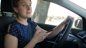 不负责任和粗心大意的在智能手机的妇女键入的消息慢动作录影,当驾驶汽车时 请用途 影视素材