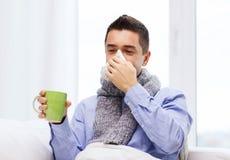 不适的人用流感饮用的茶和吹的鼻子 免版税图库摄影
