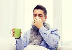 不适的人用流感饮用的茶和吹的鼻子 免版税库存图片