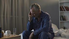 不适退休了在坐在床上和遭受头疼的睡衣的男性在晚上 免版税库存照片