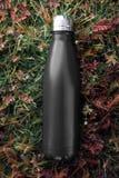 不锈的瓶热水瓶,黑颜色 在绿草背景 免版税图库摄影