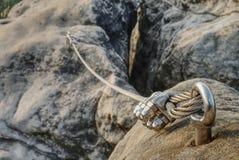 不锈的缆绳固定对安全的岩石 库存照片