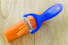 不锈钢刀子在蓝色切细红萝卜的切片机工具 库存照片