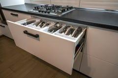 不锈钢匙子、叉子和刀子在利器在白色厨房碗柜把抽屉装箱 图库摄影