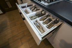 不锈钢匙子、叉子和刀子在利器在白色厨房碗柜把抽屉装箱 库存照片