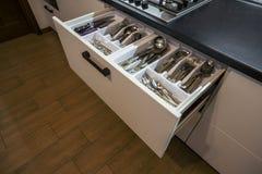 不锈钢匙子、叉子和刀子在利器在白色厨房碗柜把抽屉装箱 库存图片