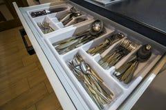 不锈钢匙子、叉子和刀子在利器在白色厨房碗柜把抽屉装箱 免版税库存照片