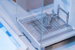 不锈钢安置的定标重量在校正试验的分析天平 库存照片
