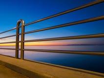 不锈钢栏杆海和海岸线在背景中 免版税库存照片