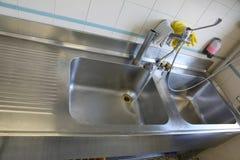 不锈钢水槽在准备的膳食一个工业厨房里 免版税图库摄影