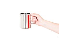 不锈钢牛奶在白色在手中隔绝的锅炉水罐 免版税图库摄影