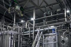 不锈钢酿造设备:大水库或坦克和管子在现代啤酒工厂 啤酒厂生产概念 免版税图库摄影
