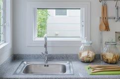 不锈钢水槽在现代厨房里 免版税库存图片