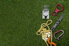 不错在绿色草坪是绳索,马枪,有刀子的一个指南针 在左边有题字的一个地方 免版税图库摄影