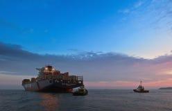 不冻港 俄罗斯- 2015年8月05日:集装箱船CMA CGM站立在路的茶花女和两猛拉在船锚 免版税库存图片