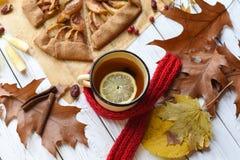 与一个上釉的杯子的一张明亮的照片热的茶、苹果饼、秋叶、肉桂条和红色编织了在白色的围巾 库存照片