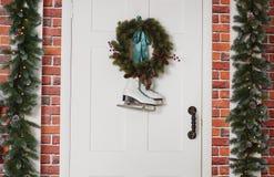 与一个云杉的花圈的白色冰鞋吊 房子的前门的圣诞节装饰 库存图片