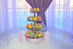 与一个五颜六色的杯形蛋糕立场的婚礼排列 库存图片