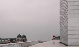 与一个人五颜六色的雨衣服的和伞的现代大厦在雨天 库存照片