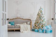 与一个典雅的沙发的时髦的圣诞节内部 舒适家 在客厅提出在树下的礼物 图库摄影