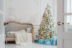 与一个典雅的沙发的时髦的圣诞节内部 舒适家 在客厅提出在树下的礼物 免版税库存图片