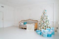 与一个典雅的沙发的时髦的圣诞节内部 舒适家 在客厅提出在树下的礼物 免版税库存照片