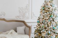 与一个典雅的沙发的时髦的圣诞节内部 舒适家 在客厅提出在树下的礼物 库存照片