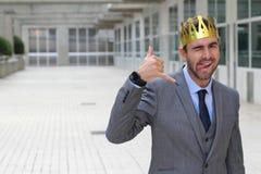 与一个冠的愉快的商人在伸出他的舌头的办公室空间  免版税图库摄影