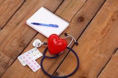 与一个医疗听诊器的心脏,在木背景 免版税库存图片