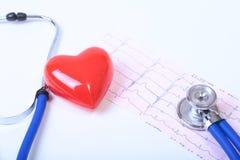 与一个医疗听诊器的心脏,在木背景 免版税库存照片