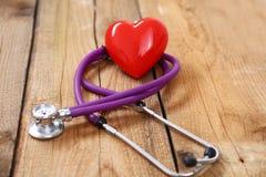 与一个医疗听诊器的心脏,隔绝在木背景 库存图片