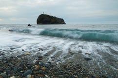 与一个十字架的岩石在海 库存照片