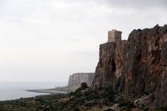 与一个古老塔的岩石峭壁,多云天空 库存图片