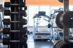 与一个哑铃的立场在健身房 免版税库存图片