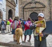 与一个喇嘛的印地安妇女姿势游人的在库斯科省,人卖pa 免版税库存照片